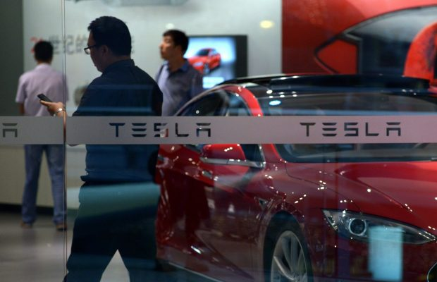 "People visit a Tesla showroom in Beijing on July 9, 2014. Electric carmaker Tesla on July 9 denounced a Chinese businessman's lawsuit seeking millions of dollars for alleged trademark infringement as an attempt to ""steal"" its property and ""without any conceivable merit"".  AFP PHOTO / WANG ZHAO        (Photo credit should read WANG ZHAO/AFP/Getty Images)"